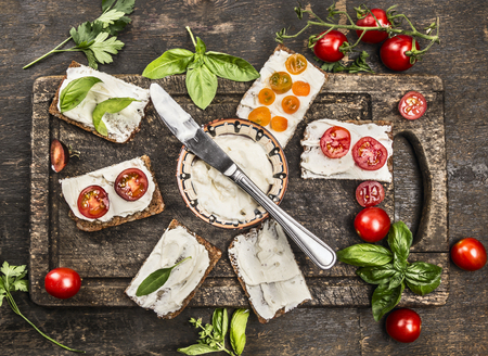 slices of bread: slice of fresh rye bread with cream cheese with basil and tomatoes on vintage wooden cutting board, viewed from above Stock Photo