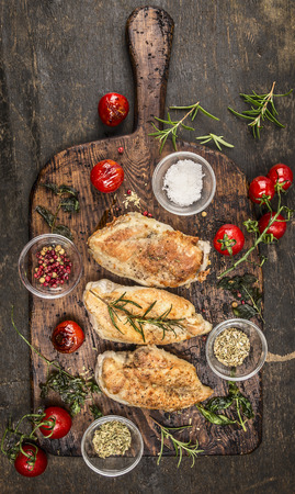 Roasted chicken breast with fried herbs and tomatoes on rustic cutting board, top view
