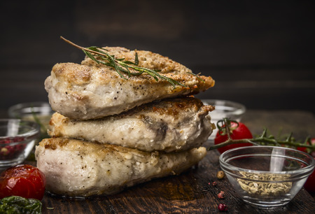 chicken breast: Stack of roast chicken breast with fried seasoning and tomatoes on dark wooden background Stock Photo