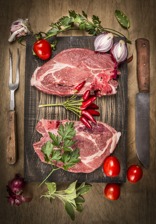 Two pork steak with meat knife and fork, fresh seasoning and spices on dark rustic wooden background, top view