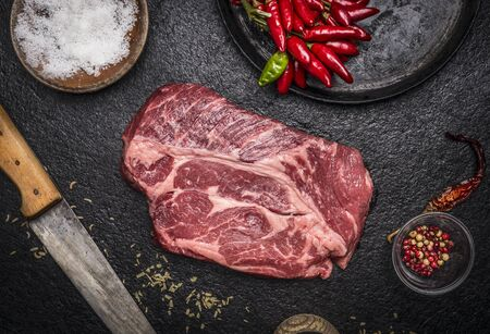 steak: fresh raw steak with red pepper salt pan carving knife on a dark rustic background top view close up