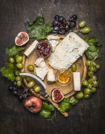 cutting boards: cheese plate with gorgonzola and Camembert cheese with Knife for cheese  white and dark grapes, honey and jam on a wooden cutting board on a dark rustic background top view close up Stock Photo