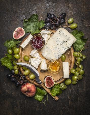 queso de cabra: plato de queso con gorgonzola y queso camembert con Cuchillo para el queso blanco y uvas oscuras, miel y mermelada sobre una tabla de cortar de madera en una visión rústica superior fondo oscuro de cerca