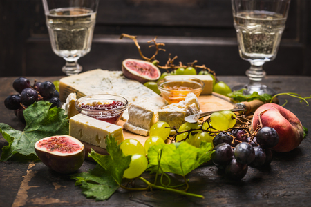 goat peach: cheese plate with white and dark grapes on a branch Peaches glasses on wooden rustic background