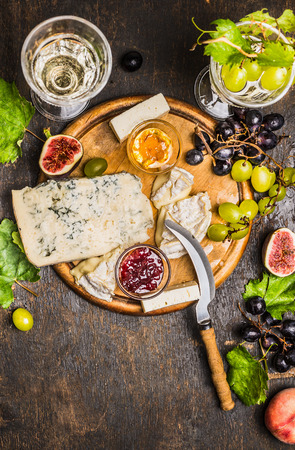 cowardly: Various soft cheeses light and dark grapes on a cutting board with a knife for cheese peach wine glasses on wooden rustic background top view close up
