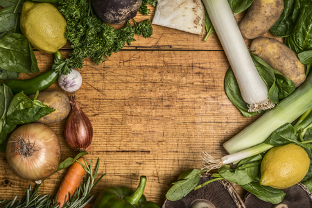 frame of fresh autumn vegetables and fruits on rustic wooden background top view