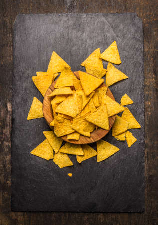nachos: Mexican nacho in a wooden bowl on dark rustic background top view