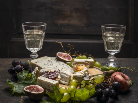goat peach: cheese plate with soft dark and light cheeses two glasses of wine grapes peaches and cheese knife on dark wooden background Stock Photo
