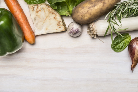 boarder: autumn fresh vegetables and fresh herbs on white rustic wooden background top view boarder