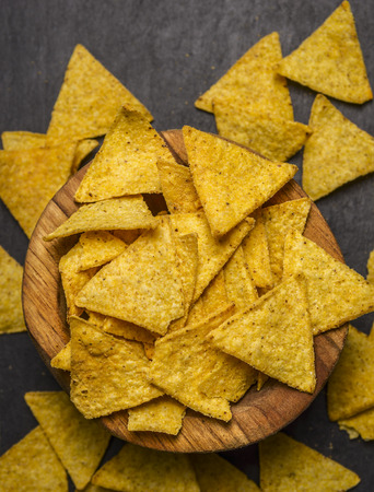collation: Mexican nacho in a wooden bowl on dark rustic background top view