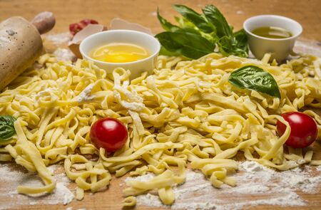 rolling up: raw homemade pasta with fresh herbs , tomatoes, flour, rolling pin ,egg and olive oil on rustic wooden background close up