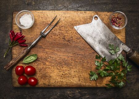 slasher: wooden cutting board with Slasher meat fork meat pepper salt tomatoes, fresh herb top view on rustic wooden background Stock Photo