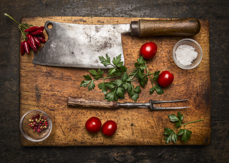 slasher: Slasher meat fork meat pepper salt tomatoes, fresh herbs on wooden cutting board top view on rustic wooden background