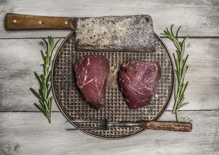 raw steak: raw beef steak on an iron pan with rosemary, meat cleaver and fork on bright, rustic wood background top view close up