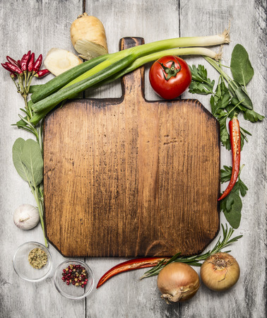 fresh autumn  and vegetables seasonings and hearbs around a wooden cutting board on bright, rustic wood background top view Фото со стока