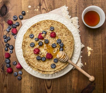 hot cakes: deliciosos panqueques con bayas frescas con miel, almendras taza de té con la cuchara de miel en plato blanco con la servilleta sobre fondo rústico de madera vista desde arriba