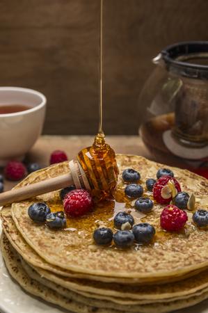 colazione: frittelle con bacche fresche e un cucchiaio di miele su fondo in legno close up