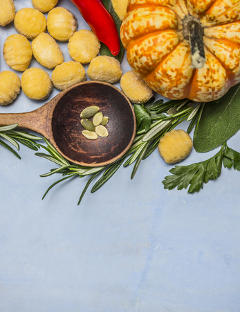 pasta: pumpkin gnocchi with wooden spoon almonds red pepper pumpkin rosemary on blue wooden background top view close up Foto de archivo