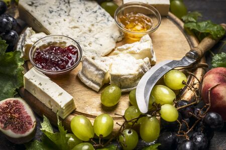 cowardly: cheese plate with Gorgonzola and Camembert cheese knife honey jam light and dark grapes on a wooden cutting board close up