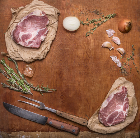 ingredients for cooking pork steaks with knife for meat and meat fork on  rustic wooden background top view,frame