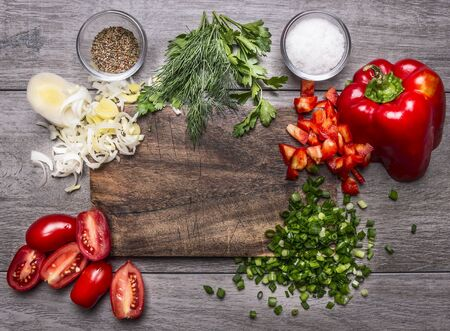 cutting: tomatoes, leek parsley and dill chopped red pepper green onion on a wooden cutting board on wooden background top view