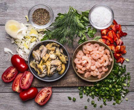 shrimps: ingredients for cooking mussels shrimp on a wooden cutting board  on wooden background top view