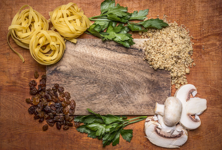italy food: pasta nest herbs chopped walnuts raisins, mushrooms on a cutting board on rustic wooden background top view