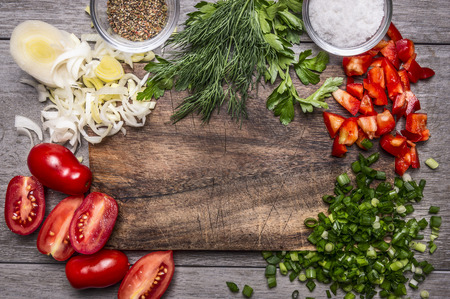 Autumn vegetables and herbs on a cutting board with spices and salt on wooden background close up top view space for text