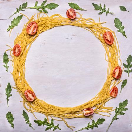 tomate cherry: ingredientes de pasta cruda tomates cherry rúcula marco alineado en el espacio vista superior de fondo de madera rústica para el texto