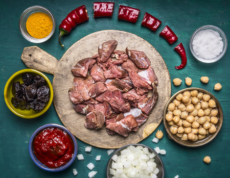 oveja negra: ingredients for cooking lamb canned chickpeas condiment hot red pepper tomato paste prunes sliced onions on a cutting board on wooden rustic background close up top view Foto de archivo