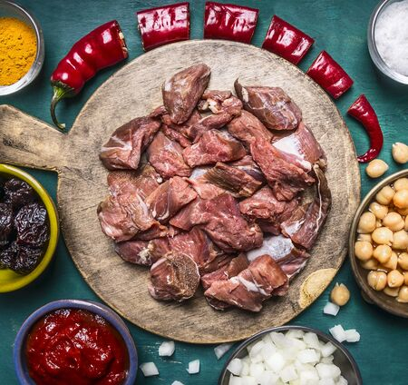 oveja negra: Fresh raw lamb with prunes part of the red pepper onion tomato paste canned chickpeas on a cutting board on wooden rustic background close up top view Foto de archivo