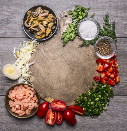 rustic food: Cooking mussels shrimp tomatoes onions parsley dill garlic seasoning salt on a cutting board frame on wooden background top view close up space for text