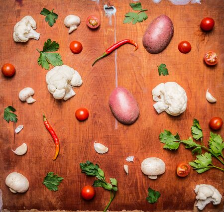 rustic food: Concept vegetarian food potatoes red pepper tomato cauliflower mushrooms on rustic wooden background top view Stock Photo