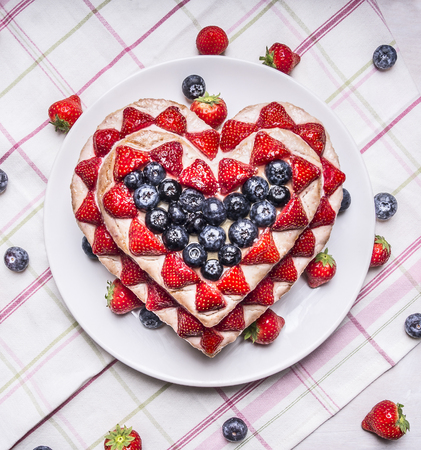 scattered in heart shaped: Homemade cake with Strawberries and blueberries for Valentines Day heart shaped on a white plate on a striped tablecloth with scattered around the berries Stock Photo