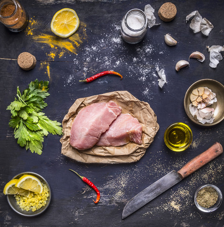 Ingredients for cooking concept Two steak of turkey with different spices lemon grass oil peeled garlic and a knife on rustic wooden background  top view