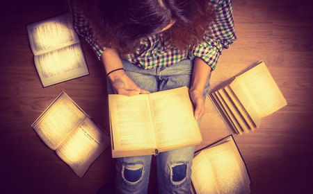 spread around: girl in a shirt holding a book sitting on the floor around her spread open books close up  retro  toning Stock Photo