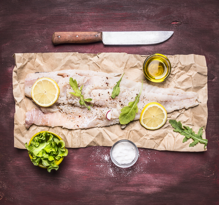 peper: Ingredients for cooking raw cod on peper knife lemon arugula lettuce salt oil on rustic wooden background top view close up