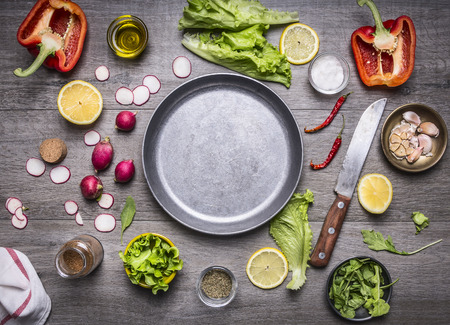 rustic food: concept cooking vegetarian food ingredients laid out around the pan with a knife and spices space for text on rustic wooden background top view