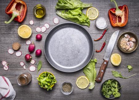 cibi: concetto cottura degli ingredienti alimentari vegetariani disposti intorno alla padella con uno spazio coltello e spezie per il testo su fondo rustico di legno vista dall'alto