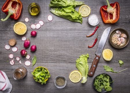 Ingredients for a vegetarian meal lettuce leaves on a lemon pepper garlic sliced radishes space for text on rustic wooden background top view Фото со стока