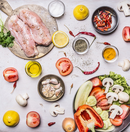 Turkey breast On a cutting board with herbs different fruits and vegetables Cucumbers mushrooms tomato salad pepper and lemon in a frying pan on rustic wooden background top view close up Stock Photo