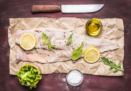 white backing: raw cod with lemon and herbs, salt and butter and a knife on paper on wooden rustic background top view close up