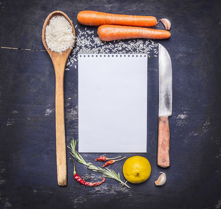 cooking ingredients: ingredients for cooking rice with vegetables, a knife, a wooden spoon, lemon, spicy, pepper, garlic lined frame with  sheet of paper text area on wooden rustic background top view close up