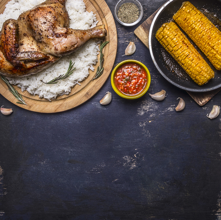 fried chicken with rice on a cutting board, hot sauce, spices, garlic and corn in the pan on dark blue wooden rustic background top view close up place for text Фото со стока