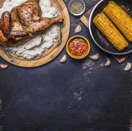 epices: poulet frit avec du riz sur une planche � d�couper, sauce piquante, �pices, l'ail et le ma�s dans la casserole sur bleu fonc� en bois vue de dessus de fond rustique close up place pour le texte Banque d'images