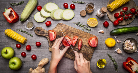red kitchen: Female hand cut tomatoes on rustic kitchen table, around lie ingredients, vegetables, fruits, and spices, Healthy foods, cooking and vegetarian concept.