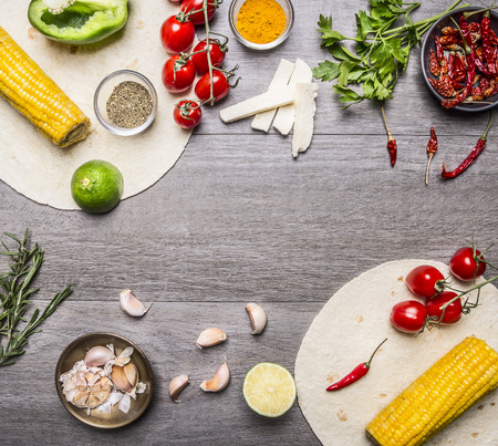 vegetarian food: ingredients for cooking vegetarian burritos lined frame, with tomatoes, pepper, spicy chili, corn, cheese and garlic border with space for text  on grey wooden rustic background top view close up