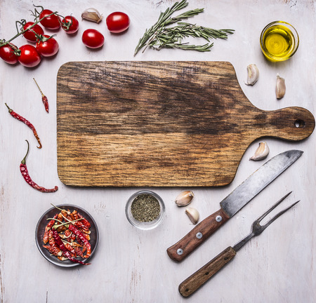 cutting board with herbs, a knife and fork, cherry tomatoes, butter and herbs around it place for text on white wooden rustic background top view Stock Photo