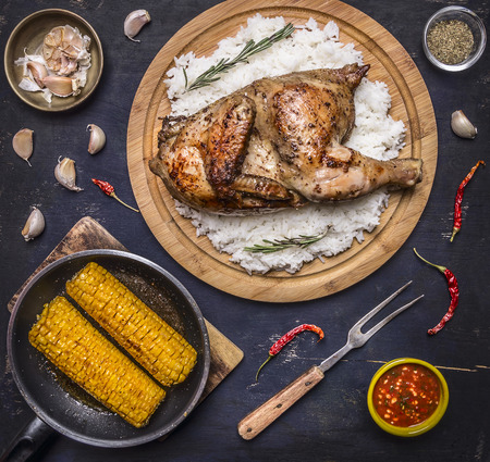 delicious fried chicken with rice on a cutting board, fork for meat, spicy sauce, spices, garlic and corn in the pan on dark blue wooden rustic background top view Фото со стока