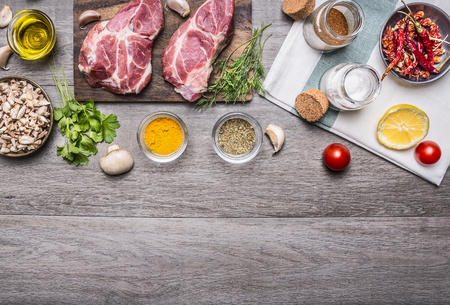 two steaks with oil and spices on cutting board with lemon, salt and meat fork, sliced mushrooms, napkin border, with text area on wooden rustic background top view Фото со стока